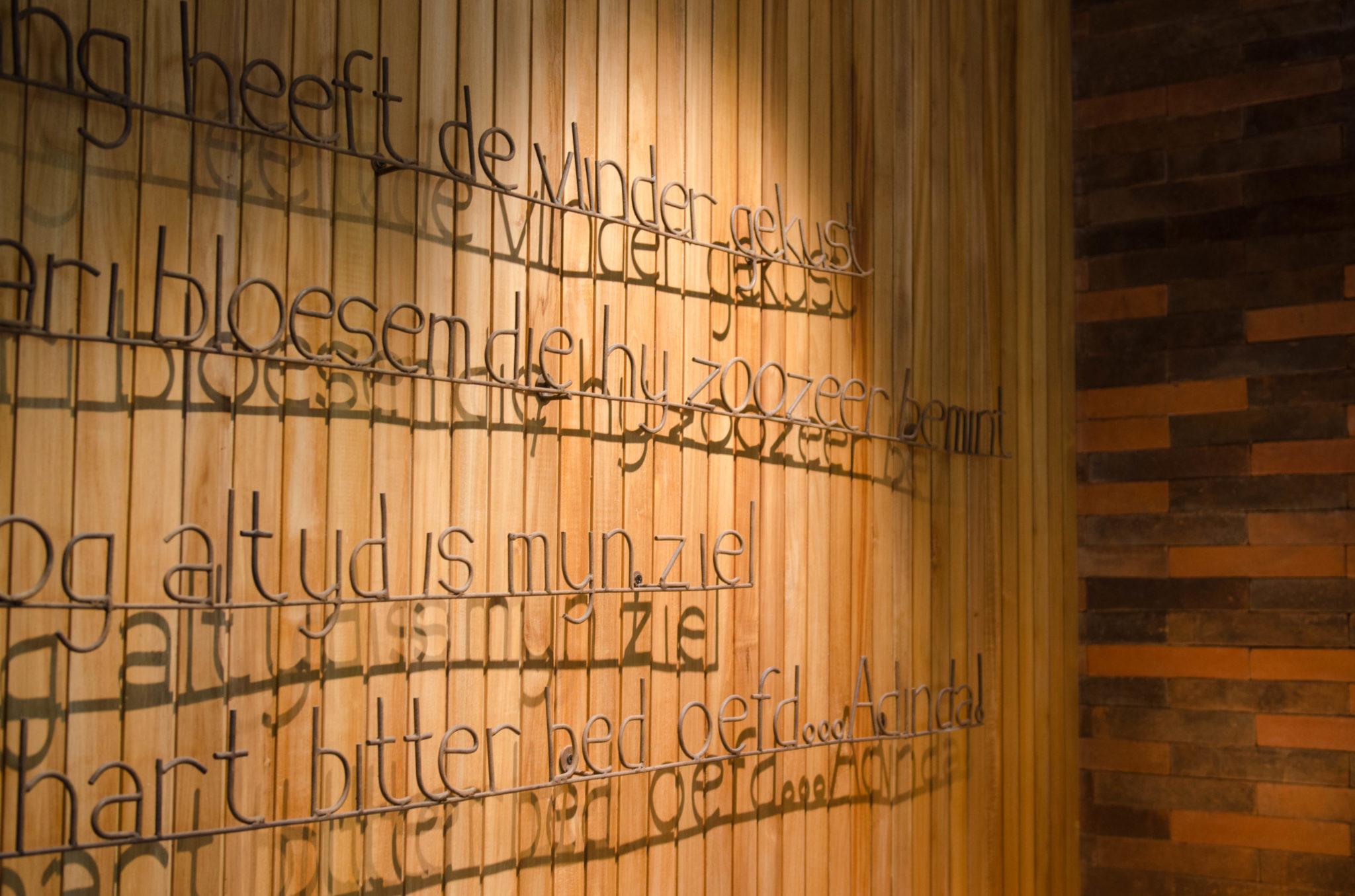 Die Wand im Hotelzimmer ziert ein Spruch