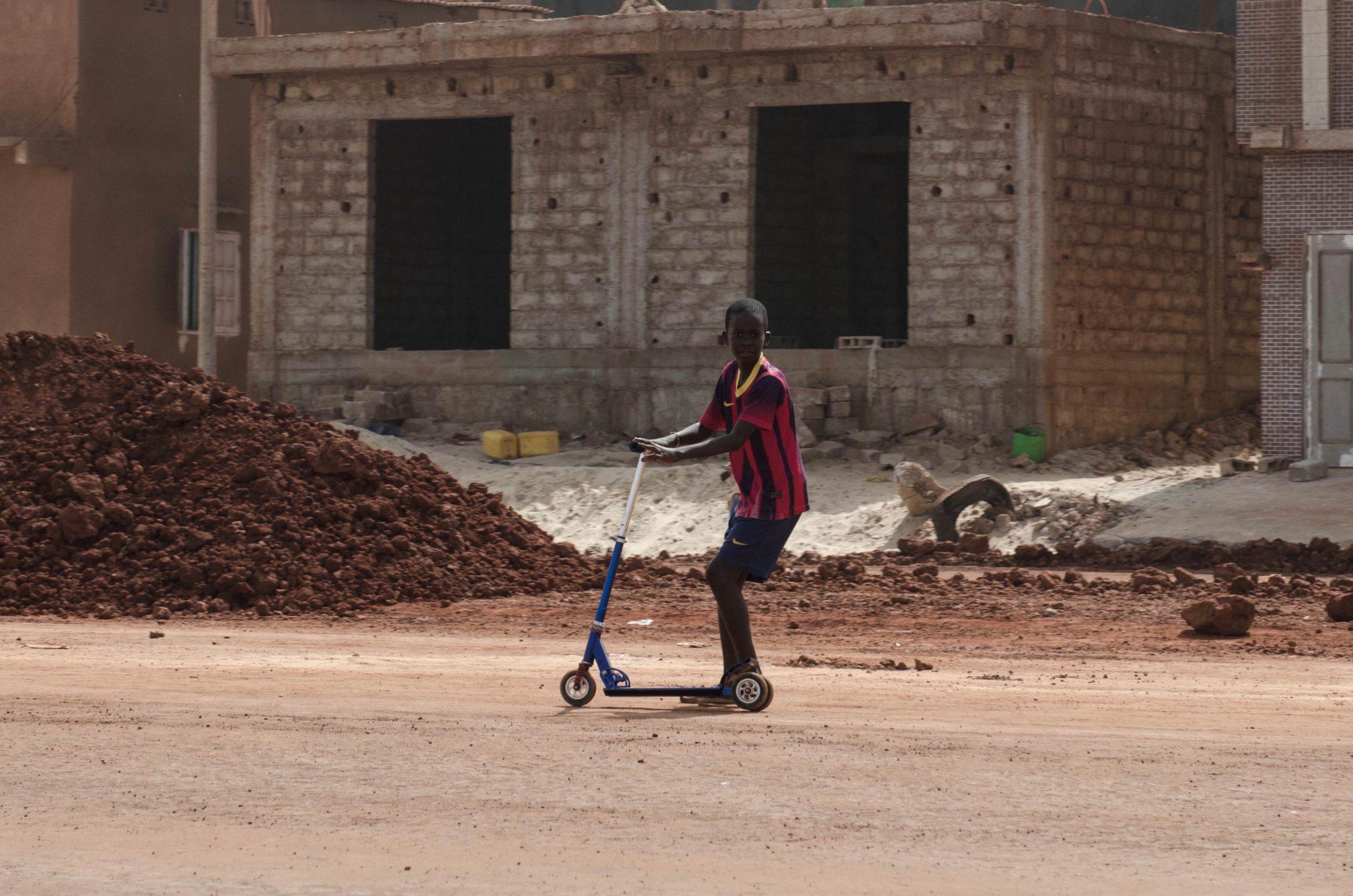 Mit dem Roller über den Sand klappt für den Jungen in Yoff Dakar ganz gut