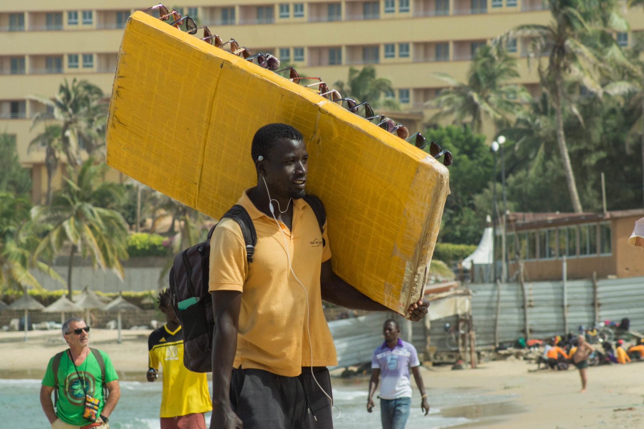 Surf Senegal: Ein Strandverkäufer mit Sonnenbrillen am Strand von Ngor in Dakar