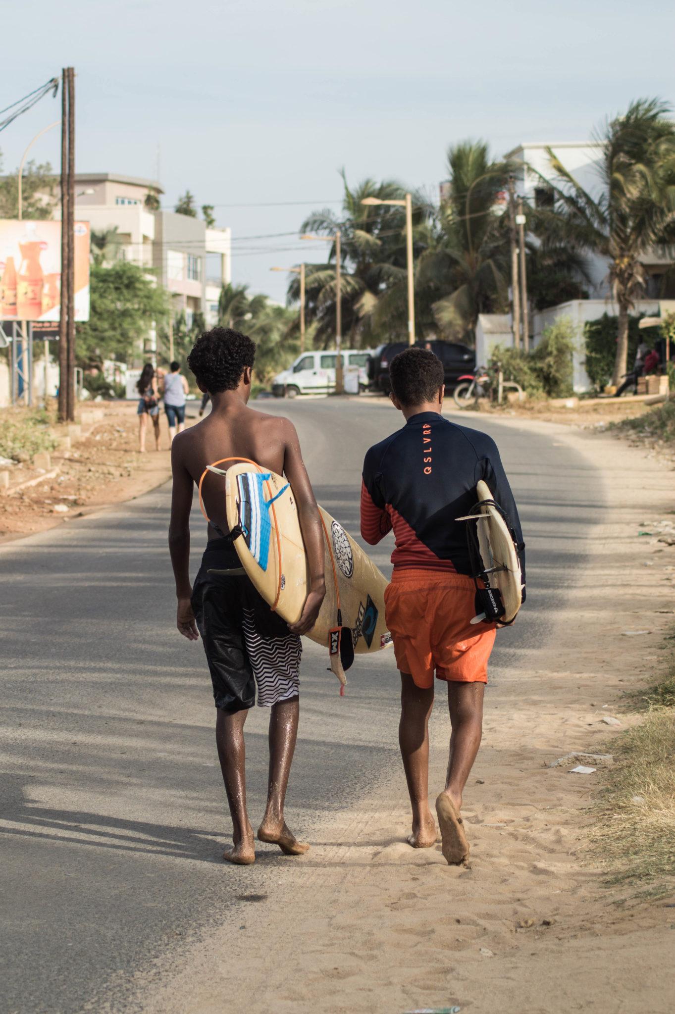 Surf Senegal: In den Straßen von Les Almadies sieht man oft junge Surfer, die mit ihren Surfbrettern nach Hause spazieren.