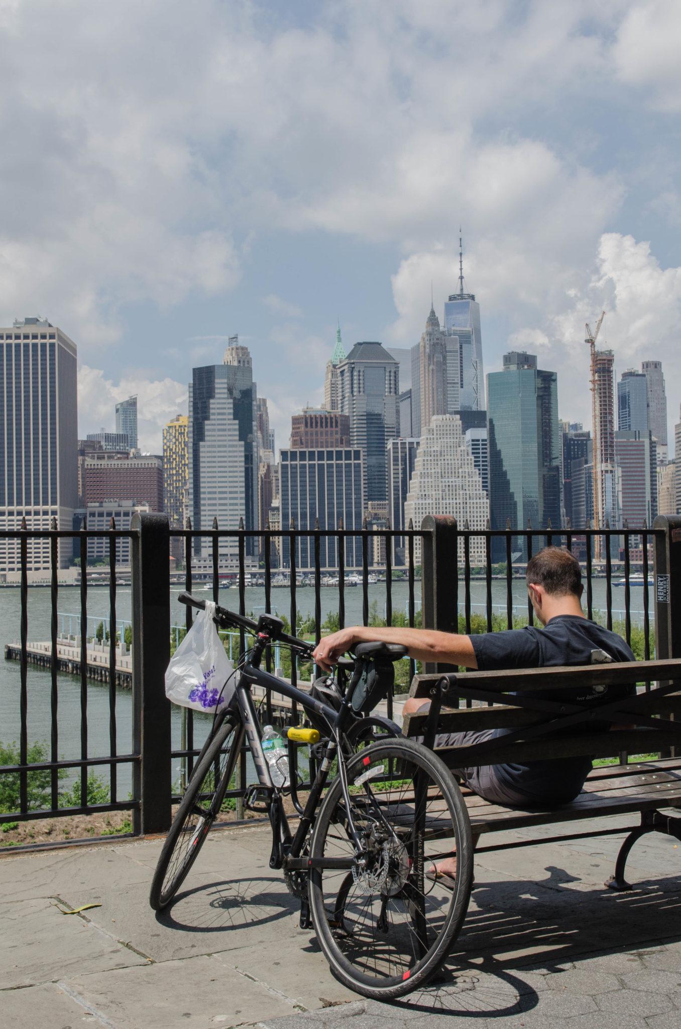 Mann mit Fahrrad vor der Skyline von New York