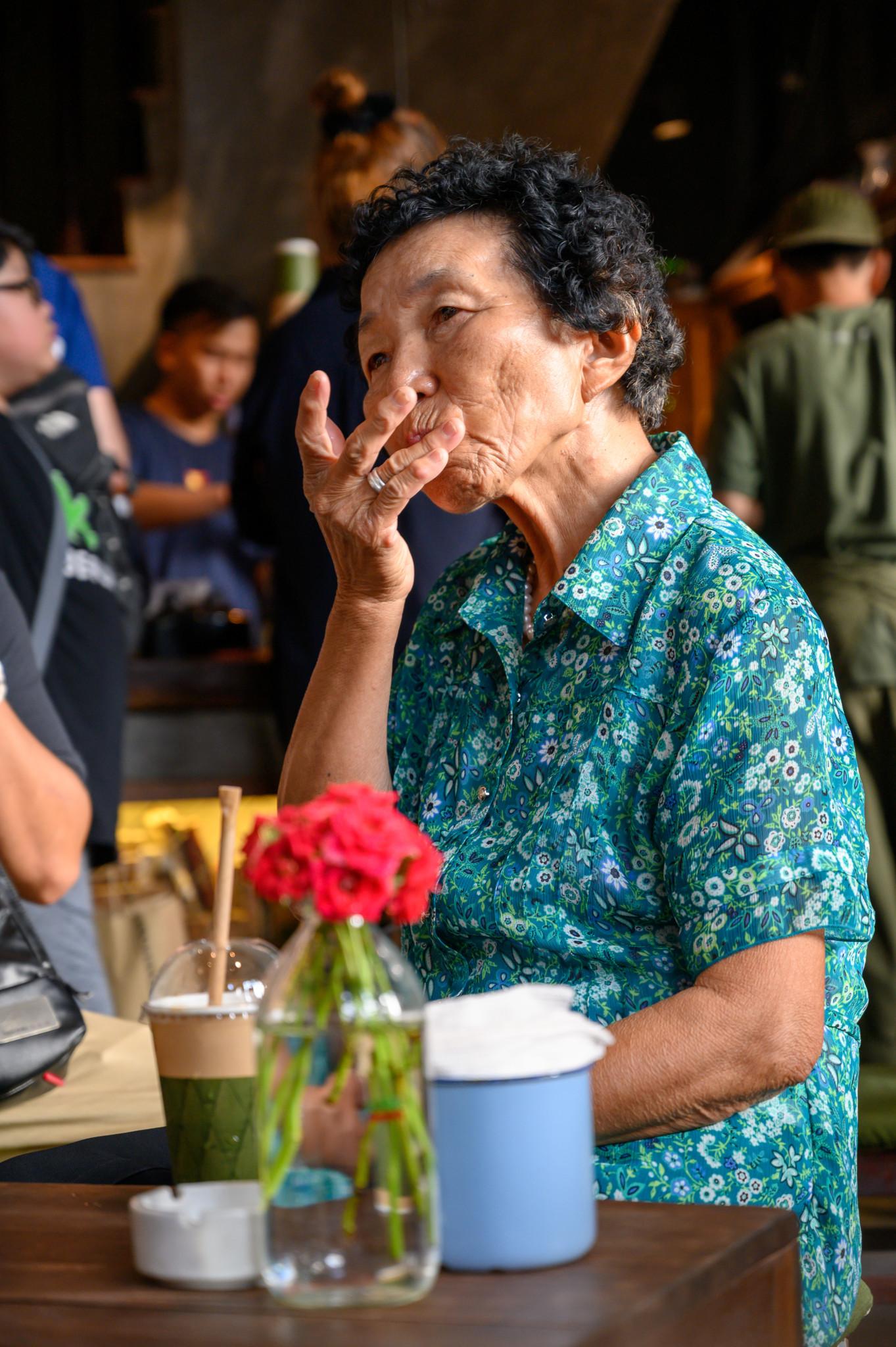 Eine alte Vietnamesin in einem Café im Old Quarter