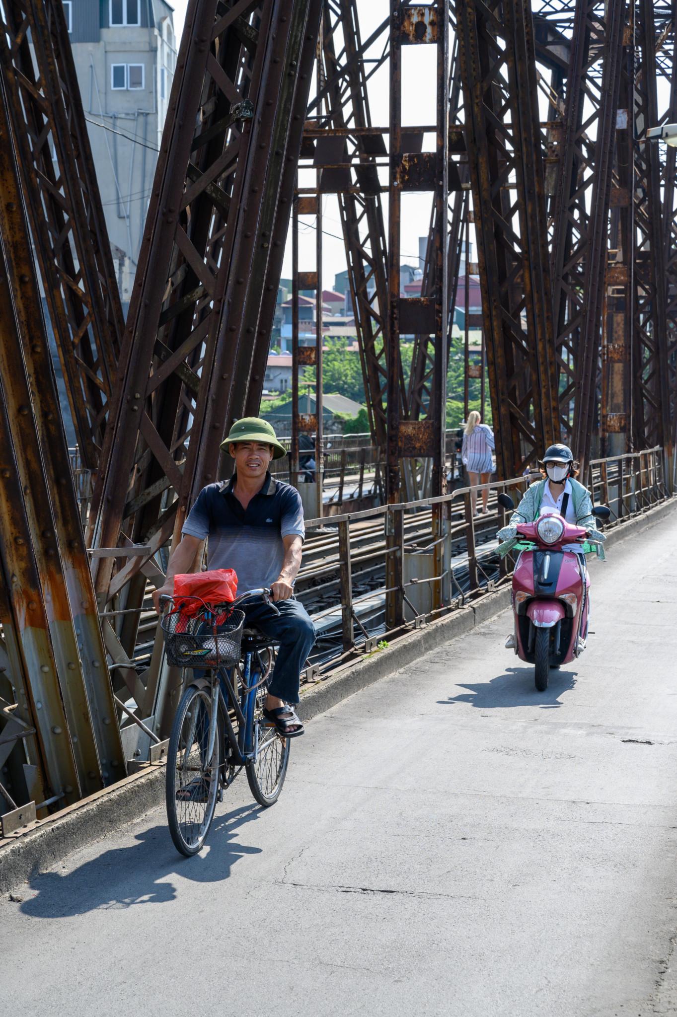 Fahrradfahrer und Rollerfahrer auf der Long Bien Brücke in Vietnam