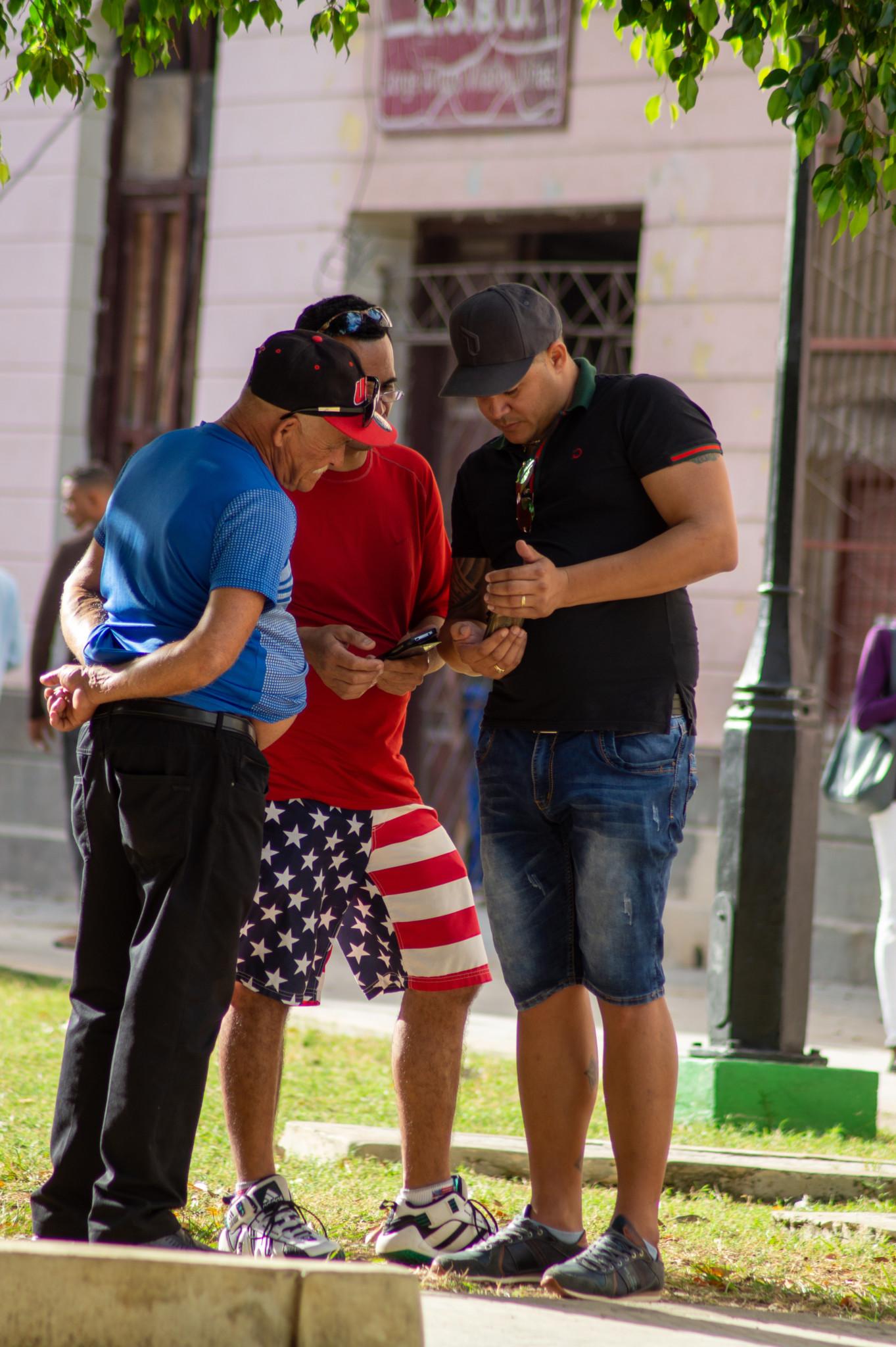Drei Männer gehen in Havanna ins Internet